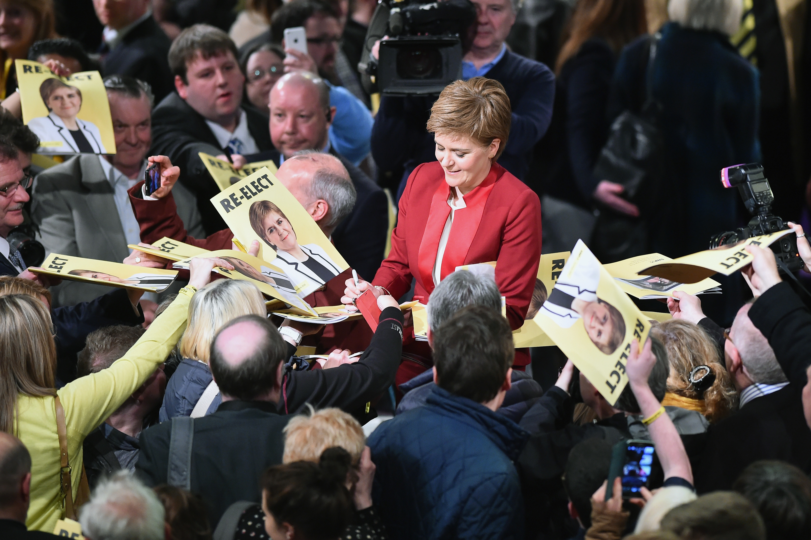 Nicola Sturgeon signs manifesto copies and posters during the launch.