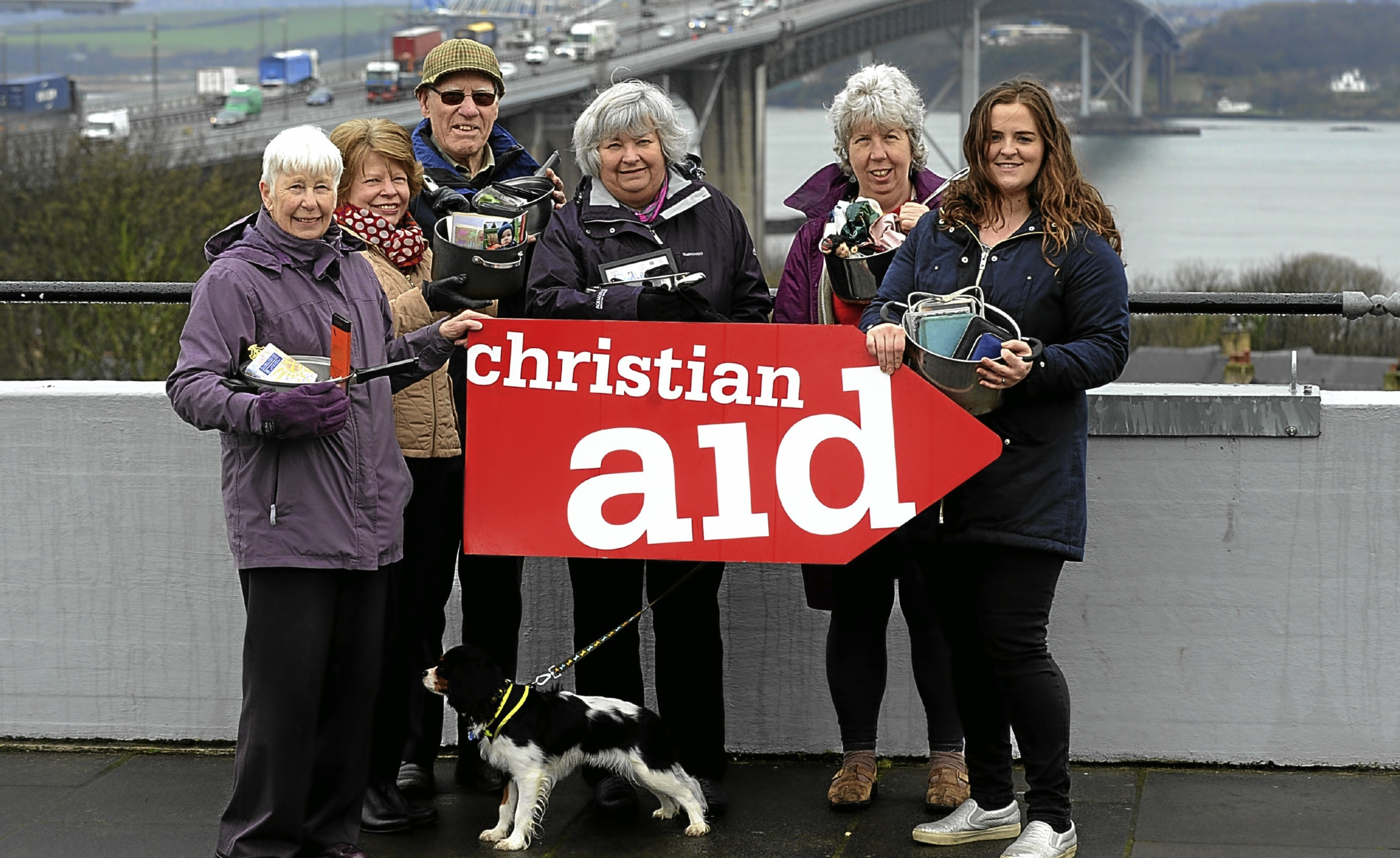 Christian Aid fundraisers Annette Carrie, Lesley MacKenzie, Tom Williamson, Gwenneth Williamson, Shenna Leslie, Amy Menzie with cooking pots which carry their most precious items. In Bangladesh, when homes flood people put their most precious items in their cooking pots to save them.The sponsored Forth Bridge Cross is 23rd April.Christian Aid Week starting the 15th May is raising funds for poor communities around the world including those in Bangladesh.