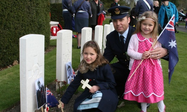 Squadron Leader Stuart McLean of the Australian Air Force was joined by his two children Georgia, 7, and Chloe, 4, in placing a cross at a grave.