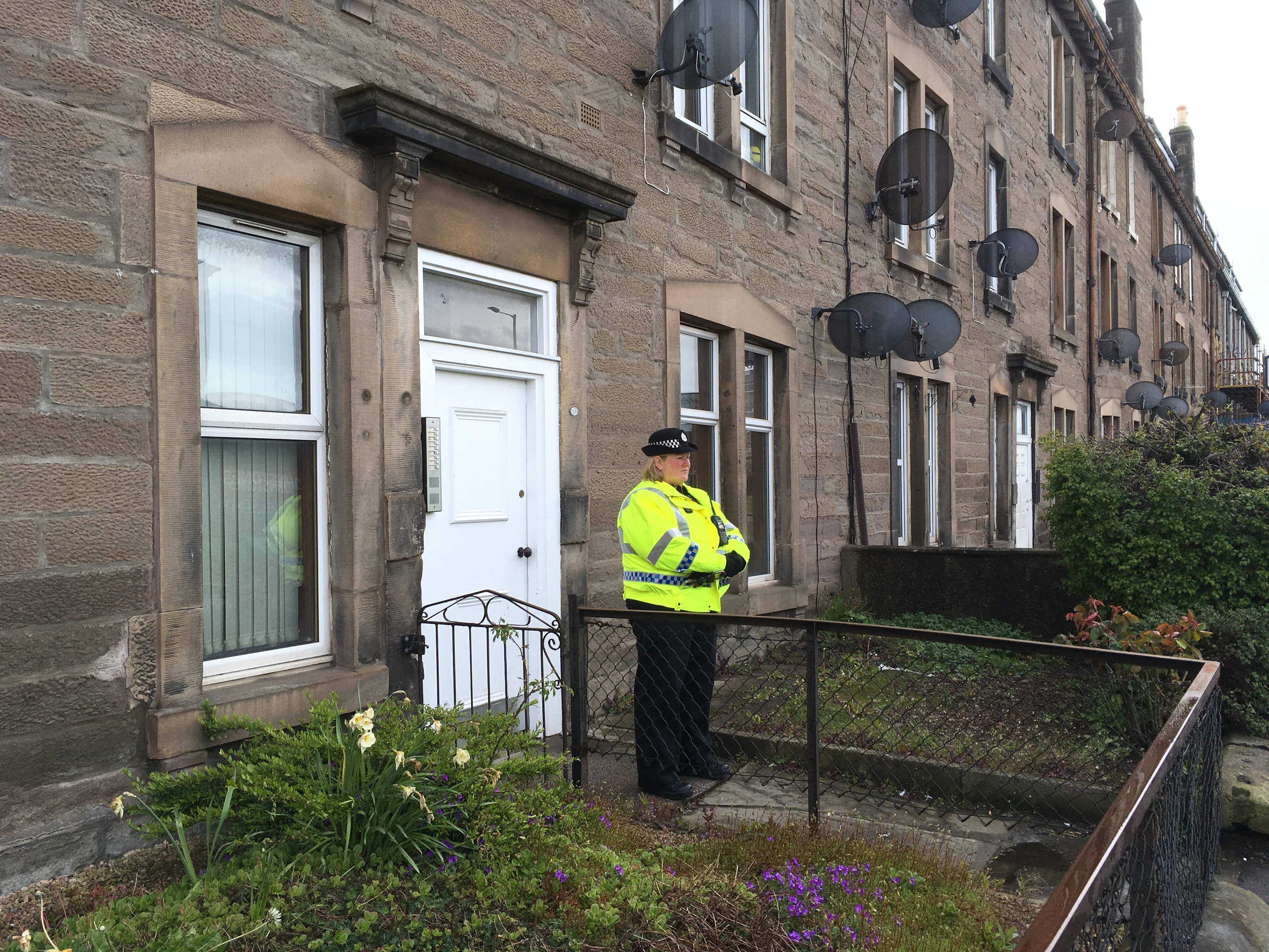 Police stand guard outside flat where woman was found dead.