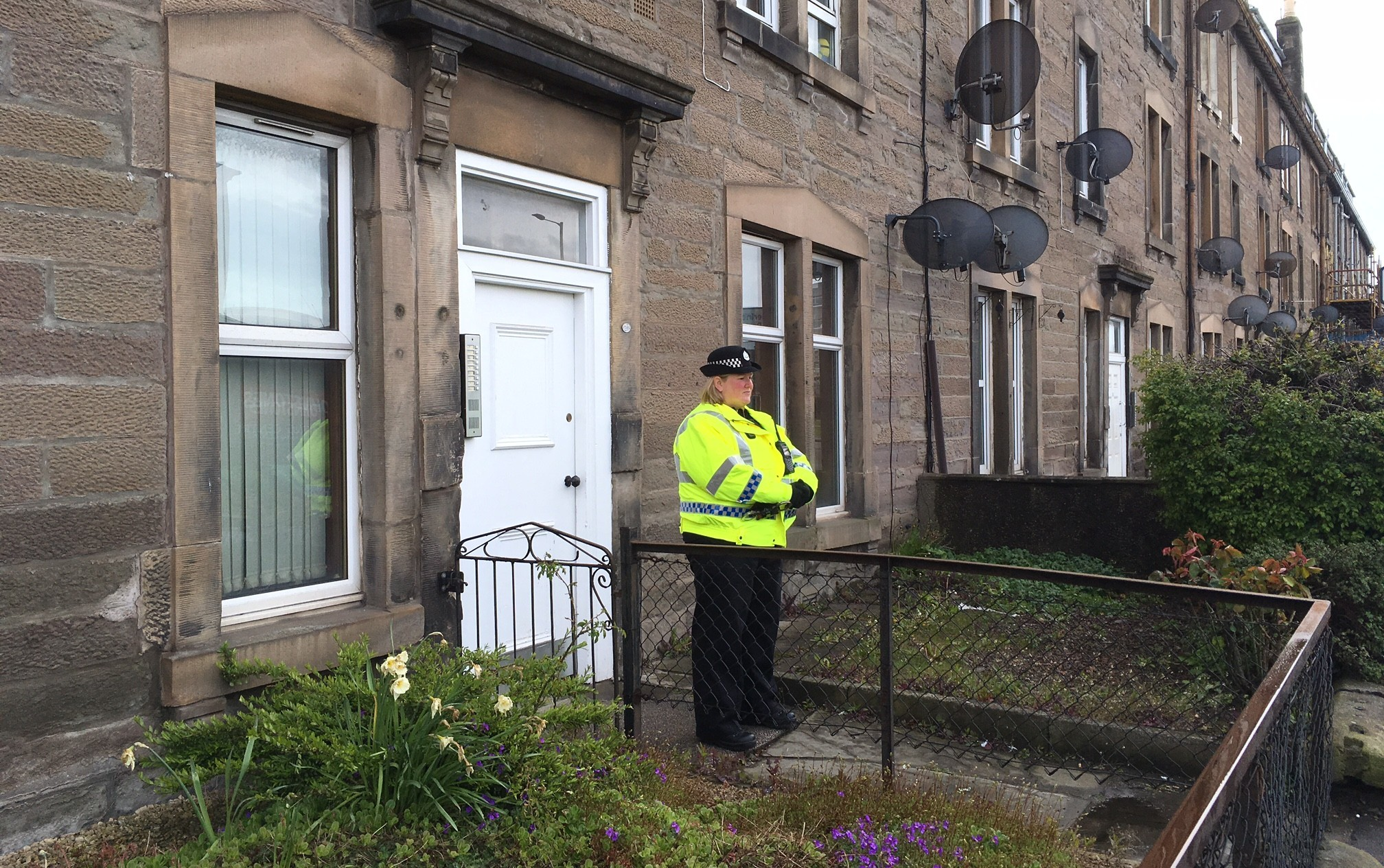 A police officer stands outside the home in Dunkeld Road where a woman was found dead.