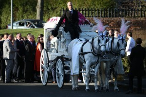Mourners walk behind a horse drawn hearse carrying Paiges coffin.