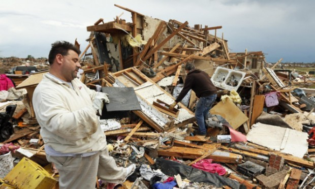 Jon Johnson, left, with brother Matt, looks at the remains of his home after the tornado ripped it apart.