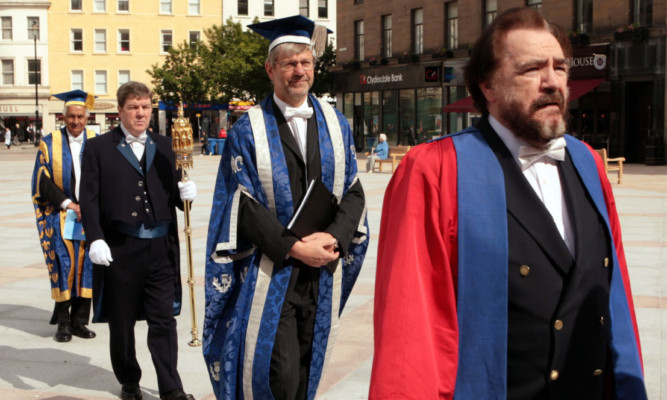 Rector Brian Cox followed by principal and vice-chancellor Professor Peter Downes as they make their way in procession to the Caird Hall.