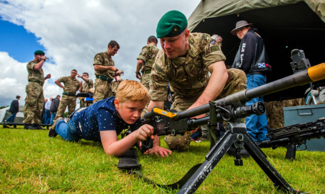 Nathan Campbell gets to grips with a general purpose machine gun, alongside Marine Sam Barton.
