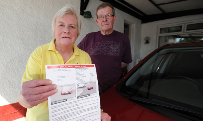 Sheona and Don Naismithwith the parking fine notice.