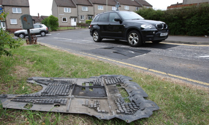 Debris from a damaged car beside the speed humps.