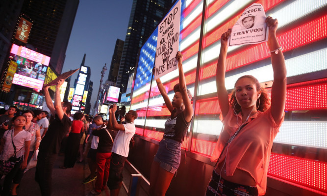 Protesters stand in front of a lit American flag in Times Square after marching from a rally for Trayvon Martin in Union Square in Manhattan.