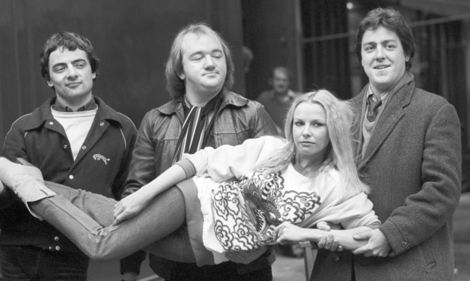 The 'Not the Nine O'Clock News's team (left to right), Rowan Atkinson, Mel Smith, and Griff Rhys Jones carrying Pamela Stephenson in 1980.
