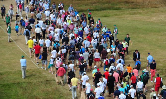 Crowds cross the 18th fairway during The Open.