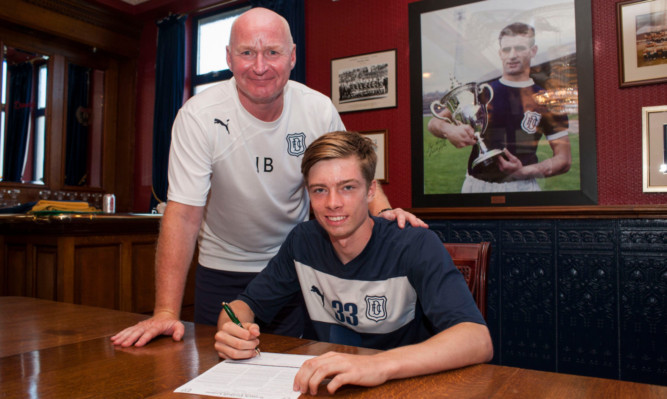 Dundee boss John Brown with teenage striking sensation Craig Wighton as he puts pen to paper on a senior contract.