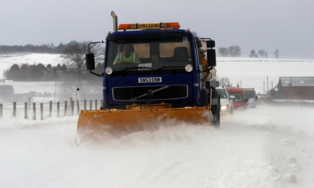 A snow plough trying trying to clear a path for drivers on the B961.