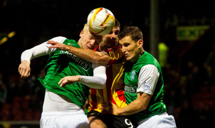 Kris Doolan, centre, battles for the ball with Hibs pair Ryan McGivern and Paul Hanlon, right.