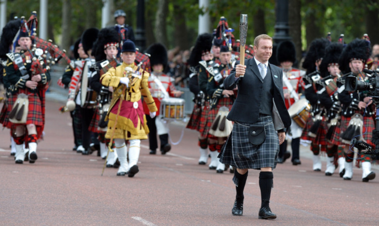 Sir Chris Hoy carries the Commonwealth Games baton along The Mall to Buckingham Palace in central London.