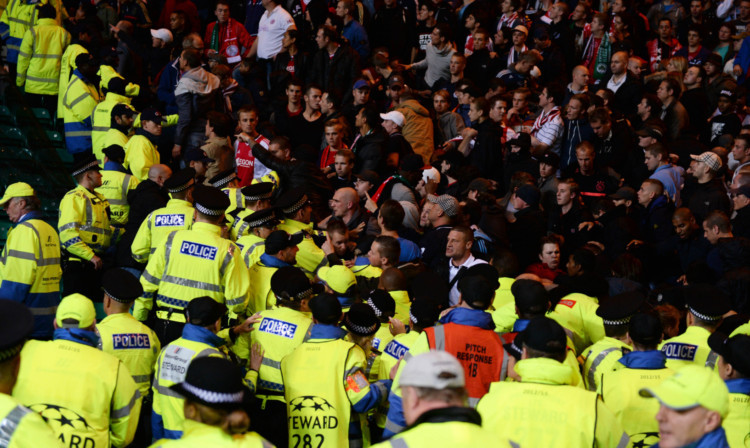 Police and stewards dealing with Ajax fans in the aftermath of Celtic's opening goal.