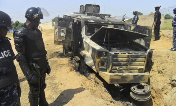 Police at a burnt-out army personnel carrier following an attack by Boko Haram in Damaturu, Nigeria. The Islamic extremists have also stormed a college, killing around 40 students.
