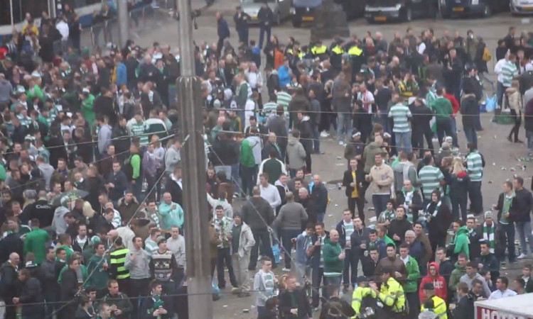 Celtic fans from Dundee have claimed they were among supporters attacked by plain-0clothed officers in Amsterdam.