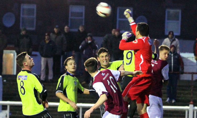 Stranraer keeper David Mitchell jumps to clear an Arbroath attack at Gayfield.