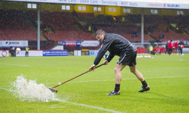 Ground staff attempt to clear the pitch of excess water.