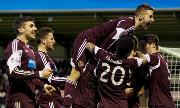 The Hearts players mob goalscorer Jamie Hamill.