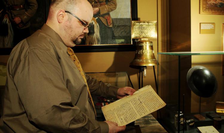 Archivist Richard McKenzie examines the letter written about the Battle of Sammara where the Baghdad Bell was captured.