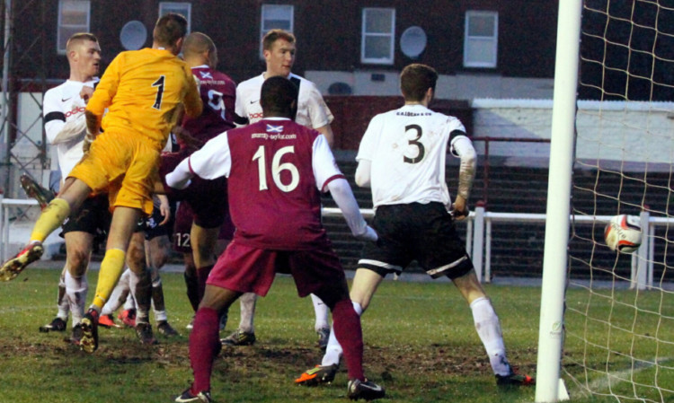 Leighton McIntosh, partly hidden by the goalkeeper, scores on his debut.