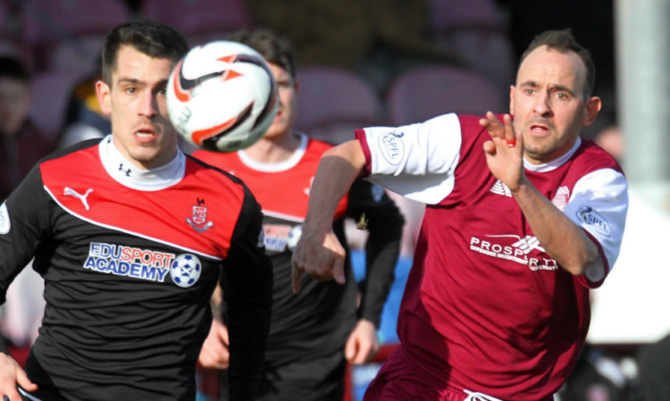 Stefan Milojevic and Arbroath's Paul McManus battle for possession.