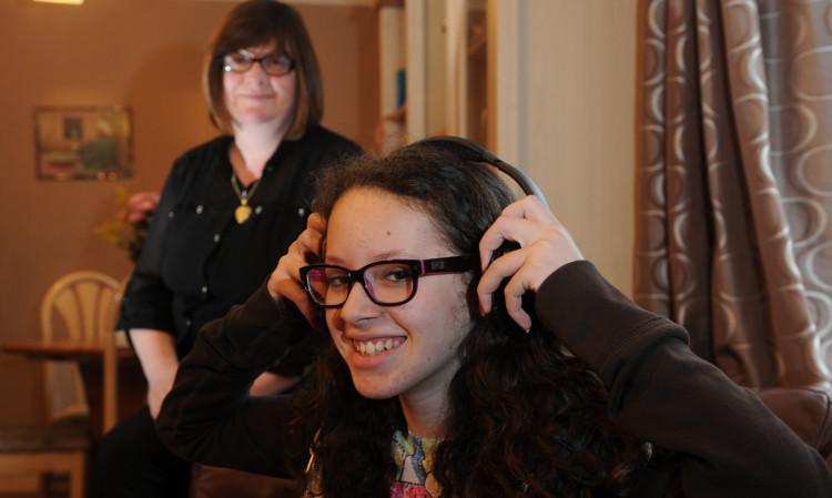 Daughter Nadia gets her hands on the Bose headphones won by mum Jacqui.