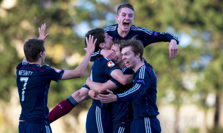The Scotland players mob scorer Jake Sheppard (centre) after his goal against Switzerland.