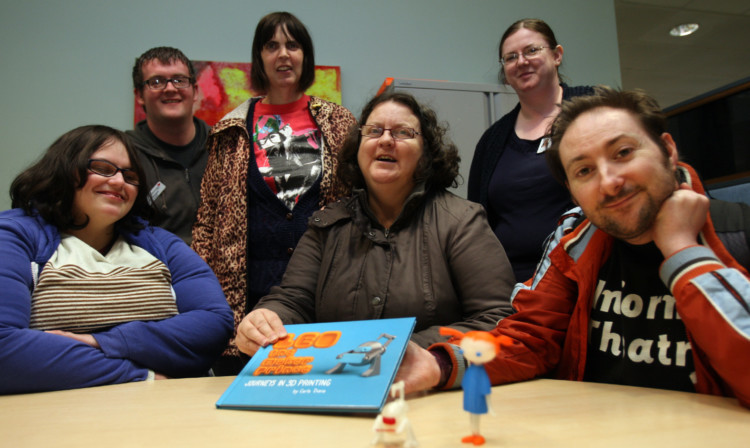 From left: Susan Gerrard, co-facilitator James Keegans, Donna Sorie, Margaret McKay, group facilitator Nicky Welch and Grahame Lapham with the book and characters created using the 3D printer at Central Library.