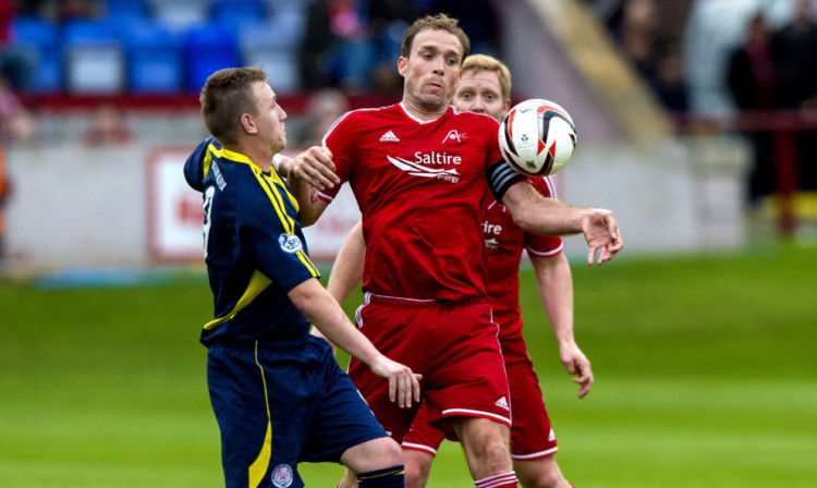 Andy Jackson battles for possession with Dons skipper Russell Anderson.
