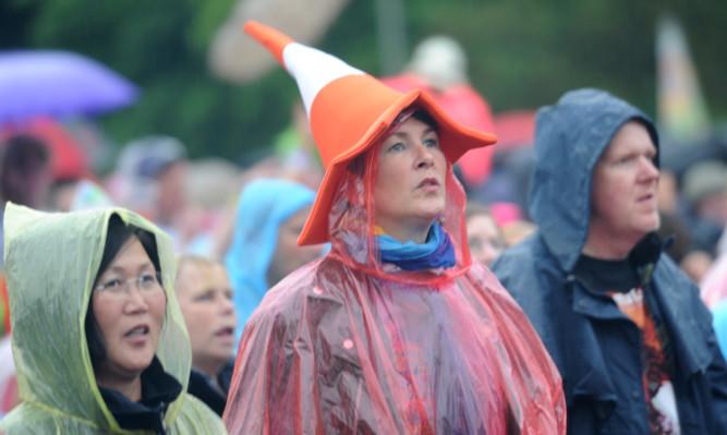 Fans enjoying Billy Ocean despite the weather.
