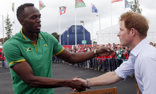 Usain Bolt meets Prince Harry during during his visit to the Commonwealth Games Village.