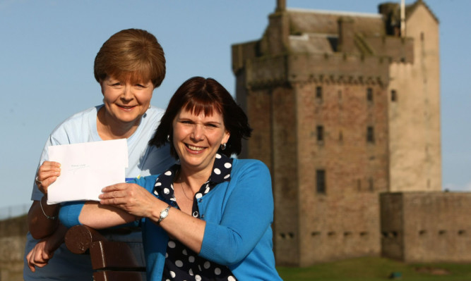 Charity swimmer Alison Anderson (right) handing over the £1245 to Hazel Mitchell.