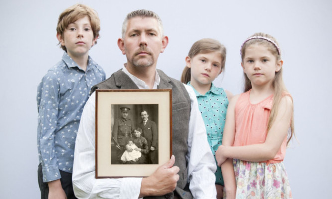 Scott Wishart with his children Alexander, Edith and May, and a photograph of his great-grandparents William and Jessie Wishart, their baby Alexander, and Williams brother, also Alexander, who served with the Cameron Highlanders.