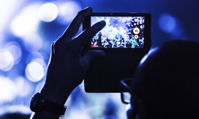 Mobile phones held aloft are now a common sight at most live performances.