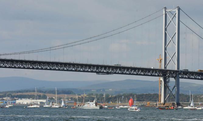 The flotilla of boats sails under the Forth Road Bridge.
