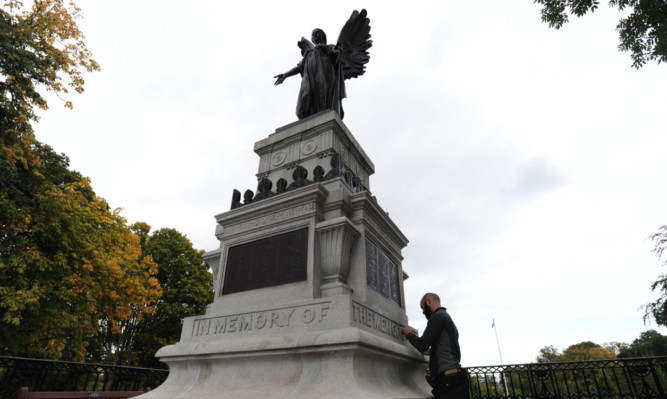 Jonathan Leburn from Graciela Ainsworth sculpture conservation puts the finishing touches to the war memorial.