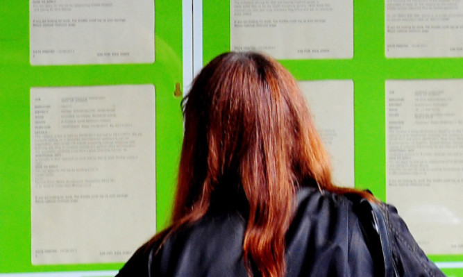 A woman searching for work in the window of a job centre.