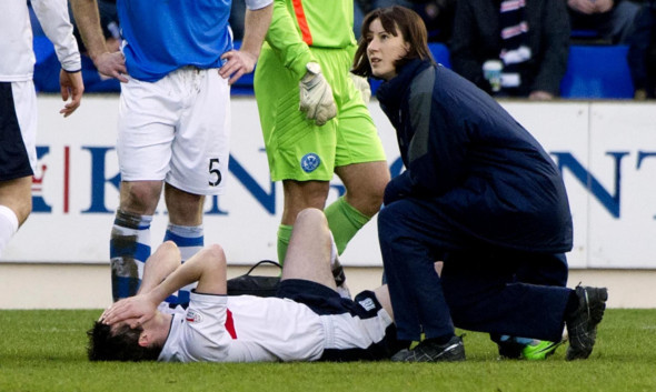 Stephen O'Donnell receives initial treatment after suffering his injury in the match at McDiarmid Park.