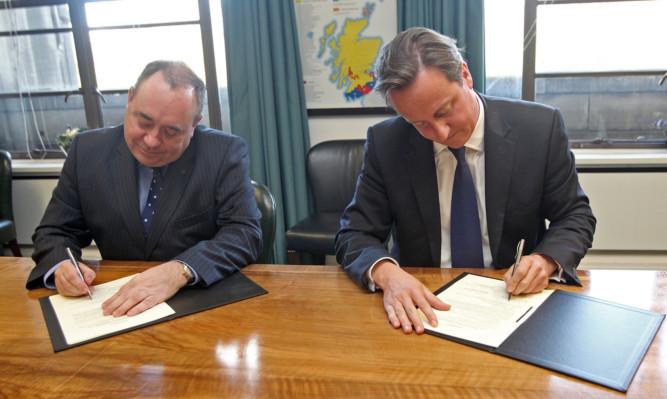 First Minister Alex Salmond (left) and Prime Minister David Cameron sign the Edinburgh  Agreement.