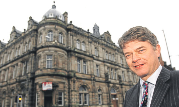 Dr Halliday with the old Post Office building that has been bought by Dundee High School.