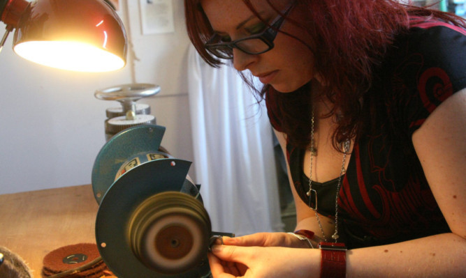 Pictured in her studio is Genna Delaney, jewellery designer.   Genna polishing one of her pieces.