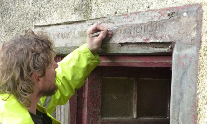 Stone conservator Eric Waanders repairs the Horn inscription.