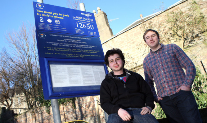 Luis Alcada and James Anthony from the church beside signs for the car park.