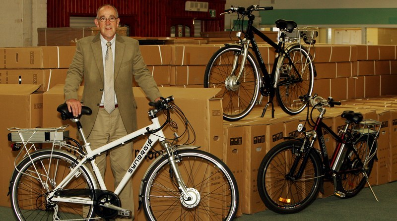 John Stevenson, Courier,08/06/10.Fife.Lochgelly,AlienOcean company making electric bikes.Pic shows AlienOcean Sales Manager Jim Stevenson with three of the current models and hundreds cretaed up and ready to be dispatched.