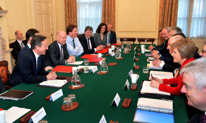Prime Minister David Cameron sits opposite First Minister Nicola Sturgeon at the meeting.