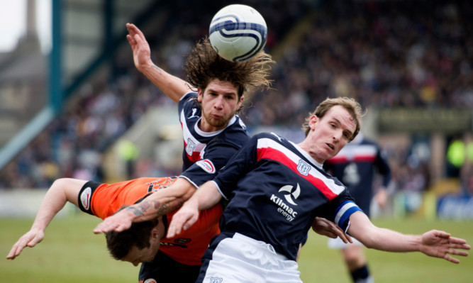 Dundee pair David Grassi (centre) and Gary Irvine crowd out Jon Daly