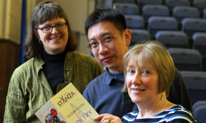 From left  Poets Erin Moure and Alvin Pang and StAnza director Eleanor Livingstone look over the festival brochure.