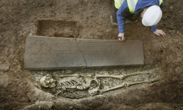 Ross Murray at the grave of a medieval knight that has been discovered under an old city car park in Edinburgh.